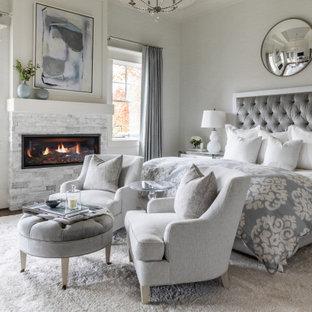 Пример оригинального дизайна: спальня в морском стиле с серыми стенами, темным паркетным полом, горизонтальным камином, фасадом камина из каменной кладки и коричневым полом