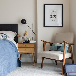 Contemporary master bedroom in London with carpet, beige walls and grey floors.