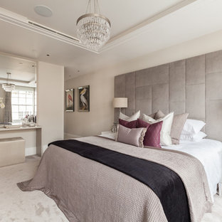 Contemporary master bedroom in London with beige walls, carpet and beige floors.
