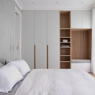 Photo of a medium sized scandi master bedroom in London with grey walls, medium hardwood flooring, no fireplace and brown floors.