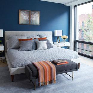 Example of a trendy light wood floor and beige floor bedroom design in New York with blue walls