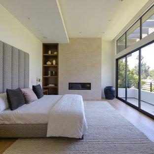 Modelo de dormitorio moderno con paredes blancas, suelo de madera en tonos medios, chimenea lineal, marco de chimenea de baldosas y/o azulejos y suelo marrón