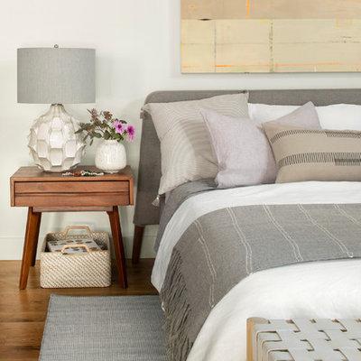 Example of a danish medium tone wood floor and brown floor bedroom design in Denver with white walls