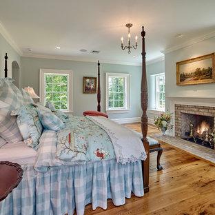 Идея дизайна: большая хозяйская спальня в классическом стиле с синими стенами, паркетным полом среднего тона, стандартным камином, фасадом камина из кирпича и коричневым полом