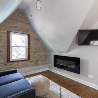 This is an example of a transitional master bedroom in Chicago with grey walls, medium hardwood floors, a hanging fireplace and brown floor.