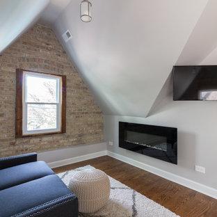 Inspiration pour une chambre parentale traditionnelle avec un mur gris, un sol en bois brun, cheminée suspendue et un sol marron.