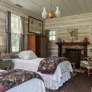 Foto de habitación de invitados de estilo de casa de campo con suelo de madera oscura, chimenea tradicional y marco de chimenea de ladrillo