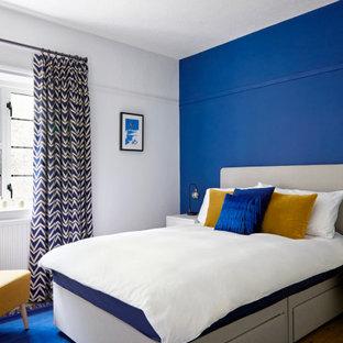 サリーのコンテンポラリースタイルのおしゃれな客用寝室 (無垢フローリング、暖炉なし、茶色い床、青い壁)