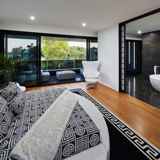 Contemporary master bedroom in Perth with white walls, medium hardwood floors and brown floor.