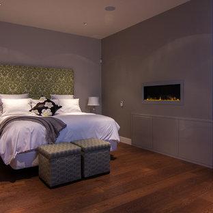 Bild på ett funkis sovrum, med grå väggar, mellanmörkt trägolv, en bred öppen spis och en spiselkrans i metall
