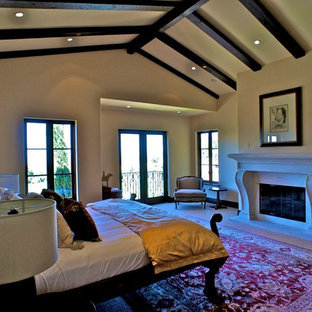 Large mediterranean loft-style bedroom in Santa Barbara with beige walls, carpet, a standard fireplace and a stone fireplace surround.