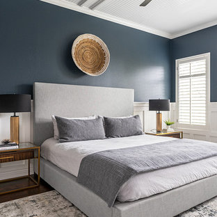 This is an example of a contemporary master bedroom in Austin with blue walls, dark hardwood floors and no fireplace.