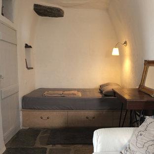 Imagen de dormitorio mediterráneo, pequeño, con paredes blancas, suelo de pizarra y marco de chimenea de piedra