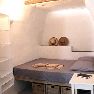 Imagen de dormitorio mediterráneo, pequeño, con paredes blancas y marco de chimenea de piedra