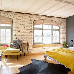 他の地域の大きいインダストリアルスタイルのおしゃれな主寝室 (ベージュの壁、淡色無垢フローリング、ベージュの床) のレイアウト