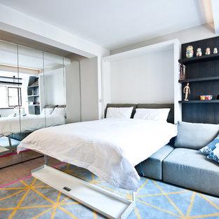 Imagen de dormitorio principal, actual, pequeño, sin chimenea, con paredes grises y suelo de madera en tonos medios
