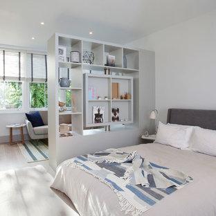 Ejemplo de dormitorio nórdico con paredes blancas y suelo de madera clara