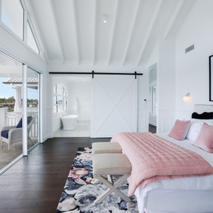 Design ideas for a beach style master bedroom in Gold Coast - Tweed with white walls, dark hardwood floors and brown floor.