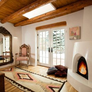 アルバカーキの中くらいのサンタフェスタイルのおしゃれな主寝室 (白い壁、淡色無垢フローリング、コーナー設置型暖炉、漆喰の暖炉まわり) のレイアウト