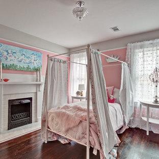 Idee per una camera degli ospiti stile americano di medie dimensioni con pareti rosa, parquet scuro, camino classico, cornice del camino piastrellata e pavimento marrone