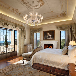 Tuscan medium tone wood floor bedroom photo in Santa Barbara with beige walls and a standard fireplace