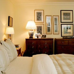 Imagen de dormitorio principal, tradicional, de tamaño medio, con paredes amarillas y moqueta