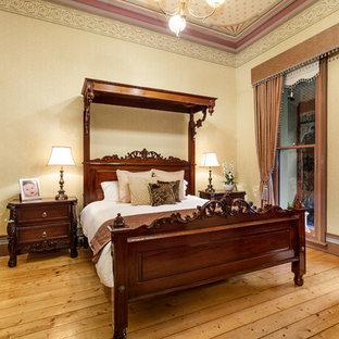 メルボルンのヴィクトリアン調のおしゃれな主寝室 (マルチカラーの壁、淡色無垢フローリング、標準型暖炉、木材の暖炉まわり、茶色い床) のレイアウト