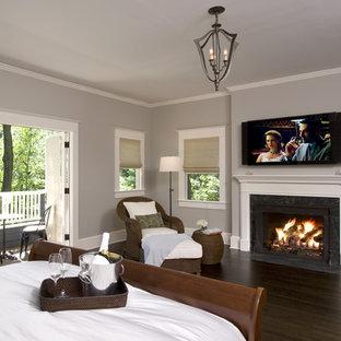 ニューヨークの中サイズのトラディショナルスタイルのおしゃれな主寝室 (グレーの壁、濃色無垢フローリング、標準型暖炉、石材の暖炉まわり、茶色い床) のレイアウト