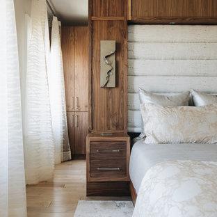 Ejemplo de dormitorio principal, actual, de tamaño medio, con paredes grises, suelo de madera clara, chimenea tradicional y marco de chimenea de baldosas y/o azulejos