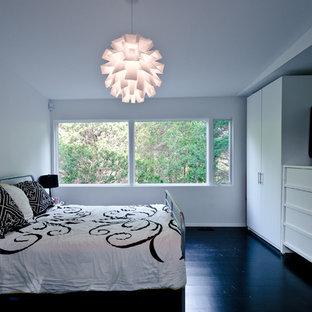 Diseño de dormitorio principal, moderno, grande, sin chimenea, con paredes blancas, suelo de madera pintada y suelo negro