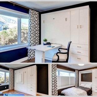 Diseño de habitación de invitados actual, pequeña, sin chimenea, con paredes negras y suelo de madera en tonos medios
