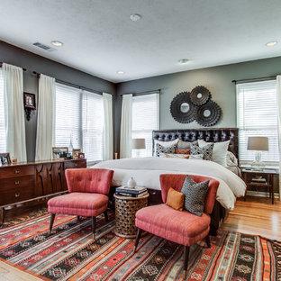 Ejemplo de dormitorio principal, clásico renovado, grande, sin chimenea, con paredes grises y suelo de madera clara