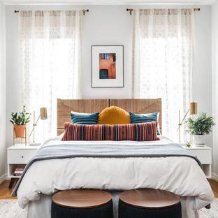 Ispirazione per una camera da letto tropicale con pareti bianche, pavimento in legno massello medio e pavimento marrone
