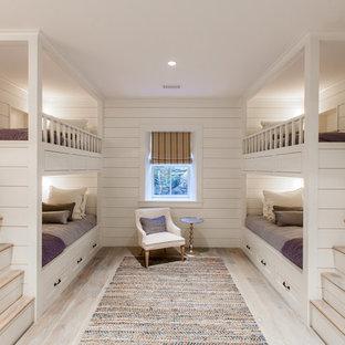 Ejemplo de habitación de invitados costera, de tamaño medio, sin chimenea, con paredes blancas y suelo de madera clara