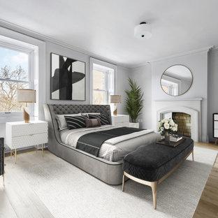 Diseño de habitación de invitados tradicional renovada, grande, con paredes grises, suelo de madera clara, chimenea tradicional y marco de chimenea de hormigón