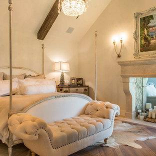 Ispirazione per una grande camera matrimoniale mediterranea con pareti beige, pavimento in legno massello medio, camino bifacciale e cornice del camino in pietra