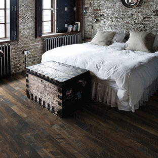 This is an example of a country loft-style bedroom in Los Angeles with dark hardwood floors, brown floor and brick walls.