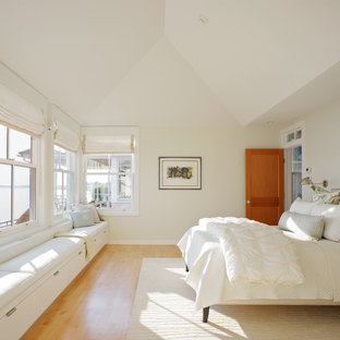 Example of a classic master light wood floor bedroom design in Providence with beige walls
