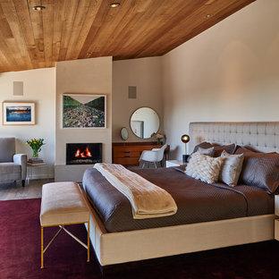 Großes Retro Schlafzimmer mit Kamin, beiger Wandfarbe, braunem Holzboden und verputzter Kaminumrandung in Seattle