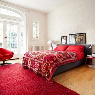 Modelo de dormitorio ecléctico, sin chimenea, con paredes blancas y suelo de madera en tonos medios