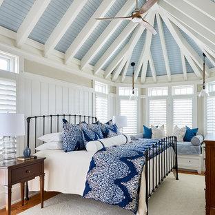 Immagine di una camera matrimoniale stile marino con pareti beige, pavimento in legno massello medio, nessun camino e letto davanti alla finestra