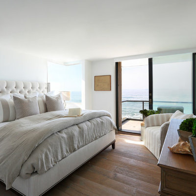 Example of a mid-sized beach style master dark wood floor and brown floor bedroom design in Santa Barbara with white walls and no fireplace