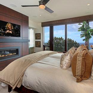 Diseño de dormitorio principal, actual, de tamaño medio, con chimenea lineal, paredes blancas, suelo de madera oscura, marco de chimenea de madera y suelo marrón