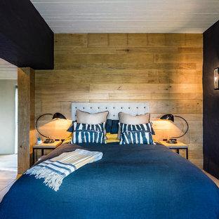 Foto di una camera matrimoniale stile marino con pareti nere, parquet chiaro e camino classico