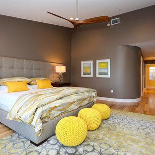 Cette photo montre une chambre tendance avec un mur marron, un sol en bois brun et un sol jaune.