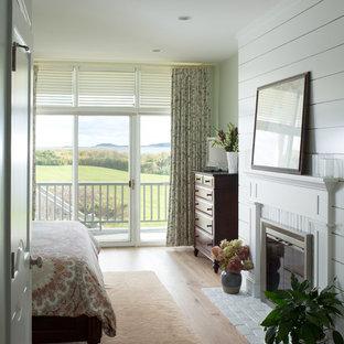Idee per una grande camera matrimoniale costiera con pareti bianche, parquet chiaro, camino bifacciale e cornice del camino in legno
