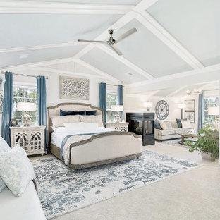 Foto de dormitorio principal, abovedado y madera, costero, extra grande, madera, con paredes beige, moqueta, chimenea de doble cara, marco de chimenea de baldosas y/o azulejos, suelo beige y madera