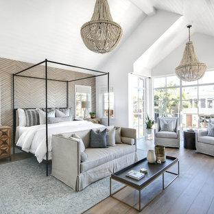 オレンジカウンティの広いビーチスタイルのおしゃれな主寝室 (ベージュの壁、無垢フローリング、暖炉なし、茶色い床)