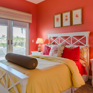 Mid-sized coastal guest carpeted and beige floor bedroom photo in Miami with orange walls and no fireplace