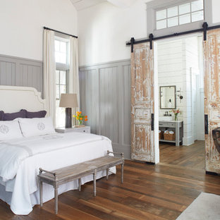 Inspiration for a beach style master medium tone wood floor and brown floor bedroom remodel with white walls